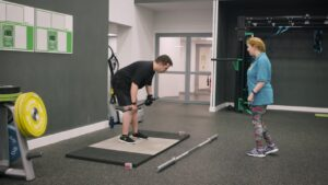 Disabled woman instructor trains a disabled man in the gym